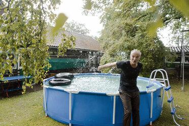 Portrait of carefree mature man enjoying summer rain at swimming pool in garden - KNSF04676