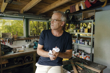 Mature man in his workshop cleaning his hands - KNSF04679