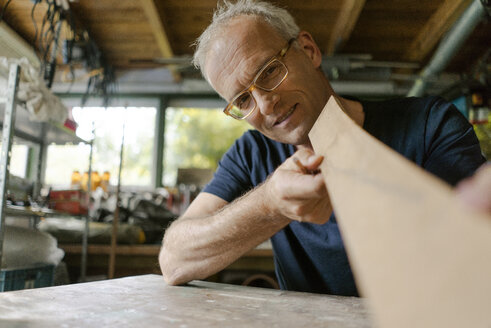Mature man working on wood in his workshop - KNSF04694