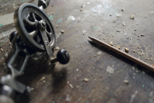Close-up of old hand drill and pencil in workshop - KNSF04700