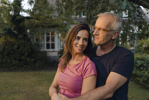Smiling mature couple in garden of their home - KNSF04703