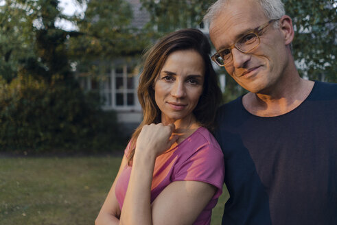 Portrait of smiling mature couple in garden of their home - KNSF04706