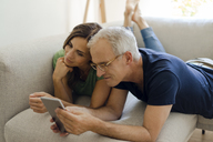 Smiling mature couple lying on couch at home sharing tablet - KNSF04709