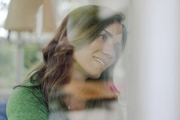 Portrait of smiling mature woman behind windowpane - KNSF04727