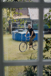Happy mature man riding bicycle in summer rain in garden - KNSF04730