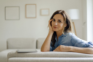 Portrait of mature woman resting on couch at home - KNSF04733