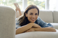 Portrait of smiling mature woman lying on couch at home - KNSF04739
