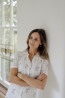 Pensive mature woman at home leaning against a wall - KNSF04751