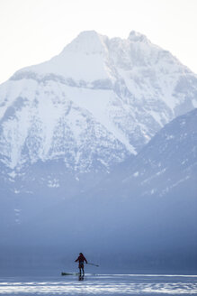 A man stand up paddle boards (SUP) on a calm Lake McDonald in Glacier National Park. - AURF02702