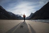 Female hiker leaves footprints in sand on scenic Horseid beach, Moskenes├©y, Lofoten Islands, Norway - AURF03113