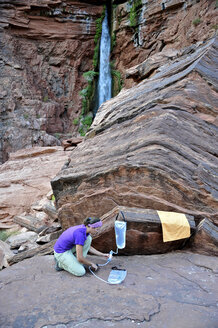 Female hiker filters water on a cliff-pinched patio near Deer Creek Falls in the Grand Canyon outside of Fredonia, Arizona November 2011. - AURF03125