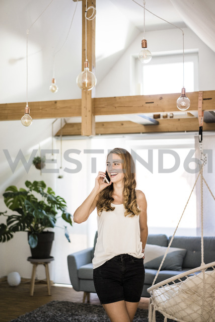 Happy woman on cell phone at home - JOSF02536