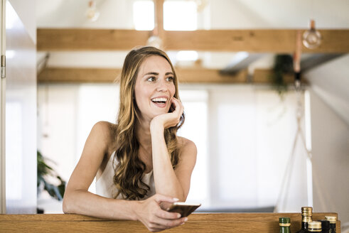 Happy brunette woman with cell phone at home - JOSF02539