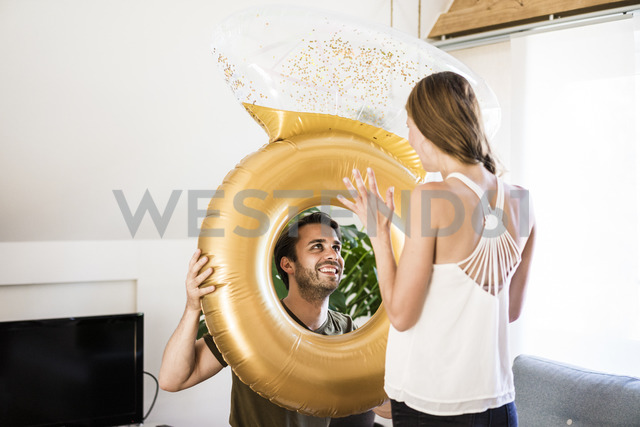Smiling man looking at girlfriend through large inflatble ring at home - JOSF02560 - Joseffson/Westend61