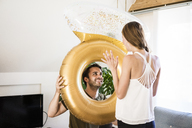 Smiling man looking at girlfriend through large inflatble ring at home - JOSF02560