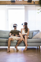 Couple sitting on couch at home wearing VR glasses playing video game - JOSF02563