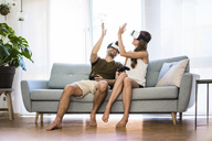 Happy couple sitting on couch at home wearing VR glasses high fiving - JOSF02566