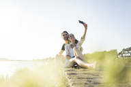 Happy couple at the riverside in summer taking a selfie - JOSF02569