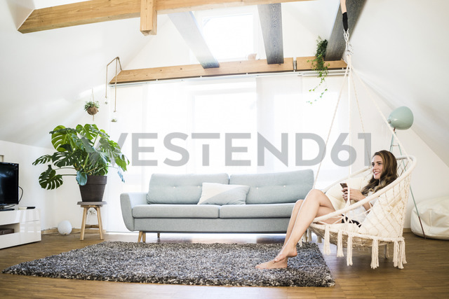 Smiling woman sitting in hanging chair with cell phone at home - JOSF02572 - Joseffson/Westend61