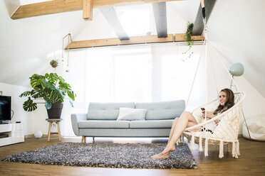 Smiling woman sitting in hanging chair with cell phone at home - JOSF02572