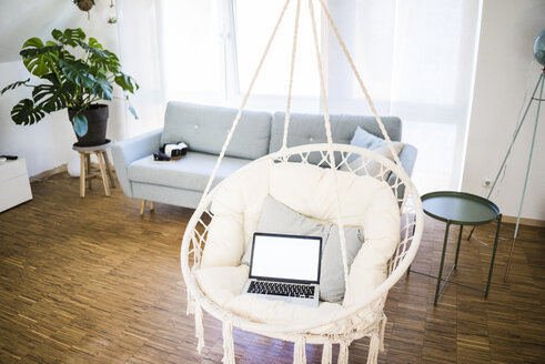 Laptop in hanging chair at home - JOSF02593