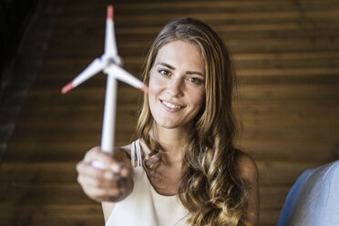 Portrait of smiling woman holding model wind turbine - JOSF02599