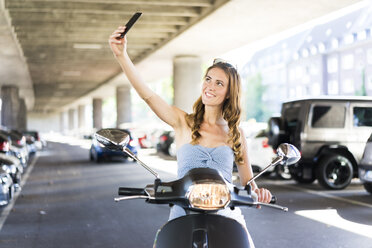 Smiling woman with motor scooter taking a selfie at underpass - JOSF02611