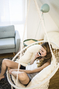 Smiling woman on cell phone sitting in hanging chair at home - JOSF02620
