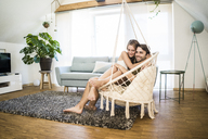 Happy affectionate couple sitting in hanging chair at home - JOSF02623