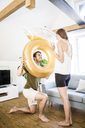 Smiling man looking at girlfriend through large inflatble ring at home - JOSF02632