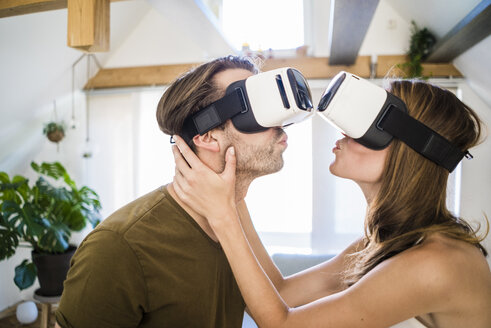 Couple wearing VR glasses kissing at home - JOSF02635