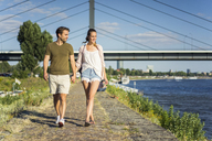 Happy couple walking hand in hand on waterfront promenade in summer - JOSF02656