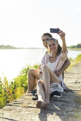 Happy couple at the riverside in summer taking a selfie - JOSF02662