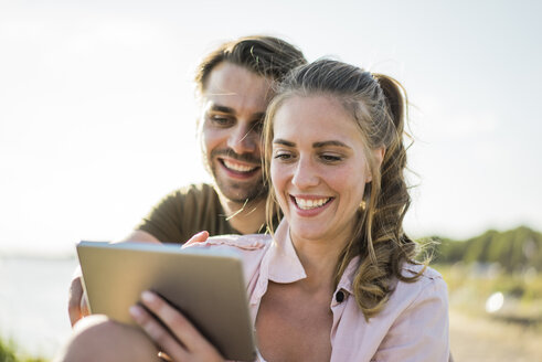 Happy couple at the riverside in summer looking at tablet - JOSF02665
