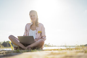 Portrait of smiling woman sitting at the riverside in summer using laptop - JOSF02668