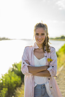 Portrait of smiling woman standing at the riverside in summer - JOSF02671