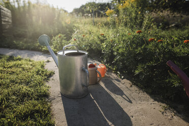 Three watering cans standing on garden path - KMKF00441