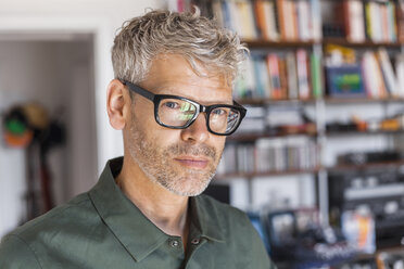 Portrait of mature man with grey hair and stubble wearing glasses at home - TCF05813