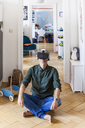 Mature man sitting on the floor at home using Virtual Reality Glasses - TCF05816