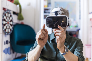 Portrait of mature man at home using Virtual Reality Glasses - TCF05819