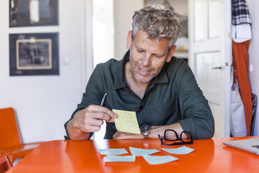 Portrait of content mature man sitting at table at home looking at notepad - TCF05822