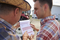 Two farmers analyzing data from clipboard on the farm - ABIF00941