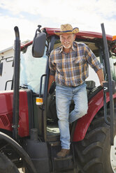Portrait of smiling senior farmer getting out of tractor - ABIF00944