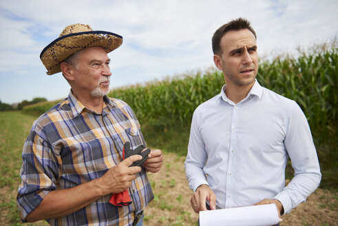 Farmer and businessman discussing on the field - ABIF00947
