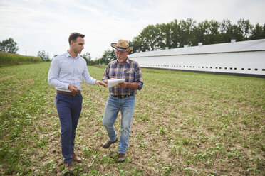 Farmer and businessman discussing data from clipboard on the field - ABIF00950