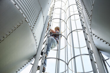 Farmer climbing up ladder at tank - ABIF00953