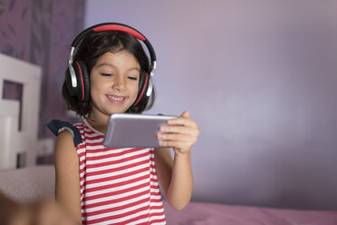 Portrait of smiling little girl listening music with oversized headphones while looking at smartphone - JASF01930