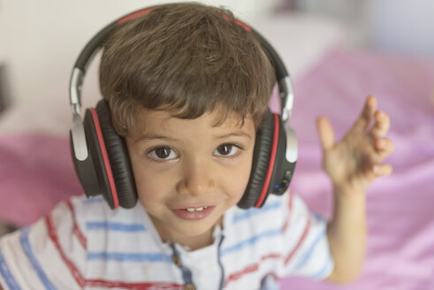 Portrait of little boy listening music with oversized headphones at home - JASF01933