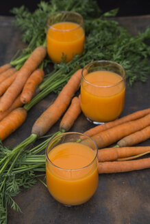 Three glasses of fresh carrot juice and carrots - JUNF01232