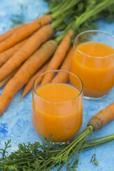 Two glasses of fresh carrot juice and  carrots on light blue ground - JUNF01235